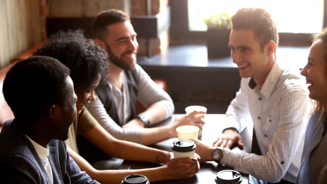 multiracial friends join hands together giving high-five at coffeehouse meeting - caffetteria video stock e b–roll