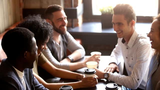 gemischtrassig freunde beitreten hände zusammen geben high-five im kaffeehaus treffen - cafe stock-videos und b-roll-filmmaterial