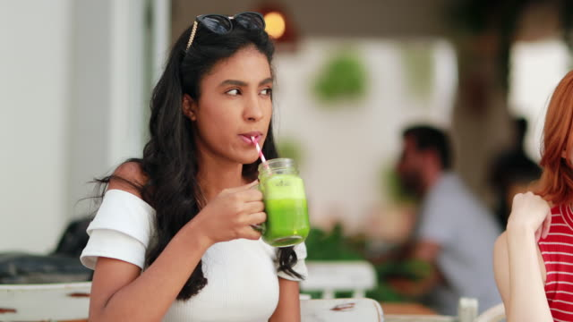 multiracial girl drinking healthy green juice outdoors - healthy green juice video stock e b–roll