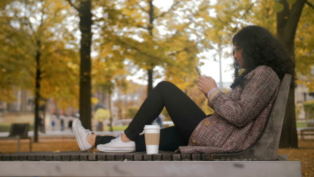 vídeos y material grabado en eventos de stock de chica multirracial en un banco de un parque de otoño toca la pantalla del teléfono inteligente y escribe pensamientos y sueños de mujeres chat mensaje - moda de otoño