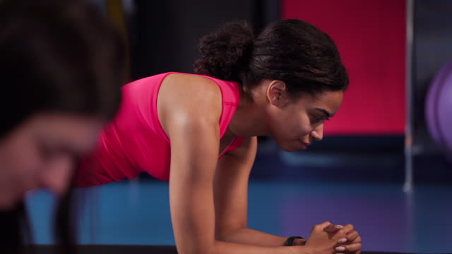 Multiracial girls standing in plank on elbows in gym video