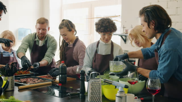 Multi-racial group of cooking class students making meals in kitchen talking to chef video