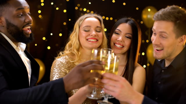 Multi-racial group of friends clinking glasses of champagne, smiling on camera