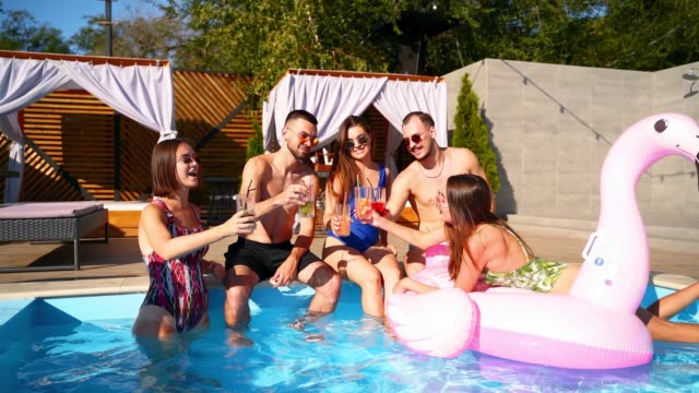 Multiracial group of friends toasting, clinking glasses with cocktails at swimming pool party. Happy young people in swimwear dancing, clubbing with inflatable flamingo, mattresses in luxury resort