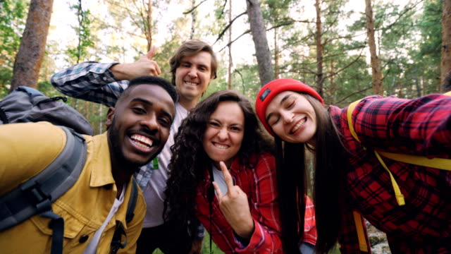 Multiracial group of friends travelers is taking selfie in wood looking at camera, posing with funny faces and gestures. Millennials are wearing modern tourist outfit.
