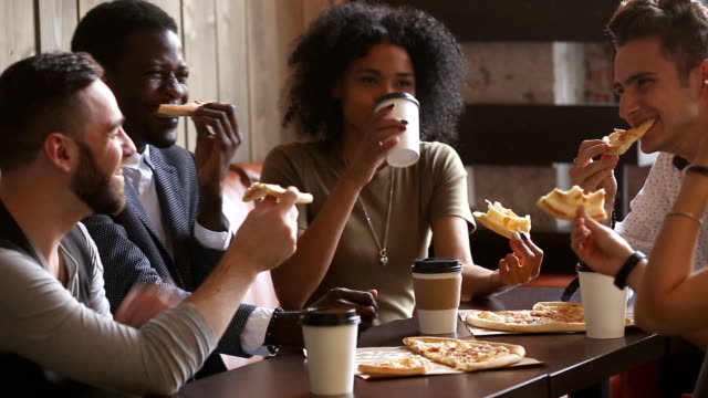 multiracial happy young people eating pizza at meeting in pizzeria - student life stock videos & royalty-free footage