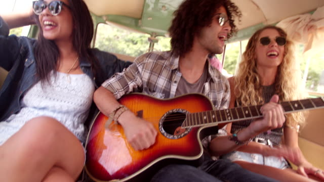 Multi-Racial Hipster friends Singing Together on road trip with guitar Two Multi Racial Hipsters, one girl and one man, playing guitar and singing together in the back of a van hippie stock videos & royalty-free footage