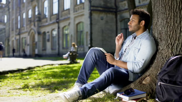 Multiracial male sitting on grass under tree, writing in notebook, creative idea video