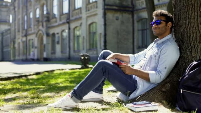 multiracial man sitting under tree wearing sunglasses, positive mood, energy - adulazione video stock e b–roll