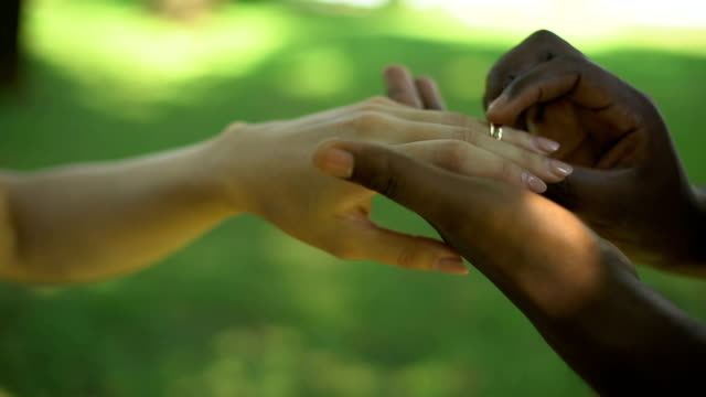 Multiracial marriage, male hand puts golden ring on brides finger, wedding time video