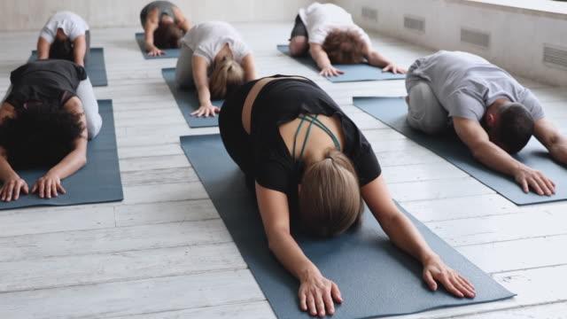 многорасовые люди, практикующие детскую позу, снижают усталость после тренировки - mindfulness стоковые видео и кадры b-roll