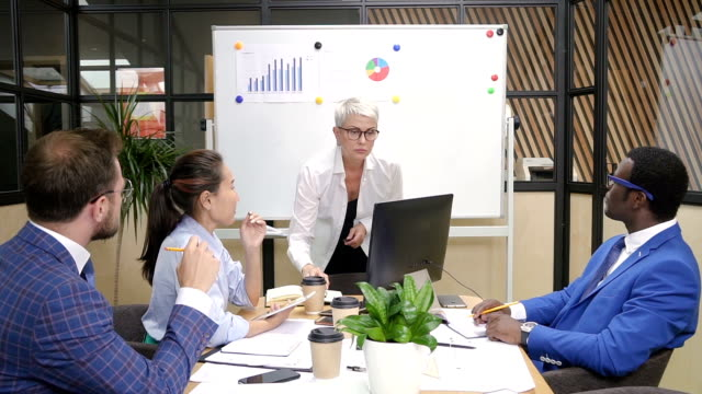 Multiracial team brainstorming financial data on briefing in modern office