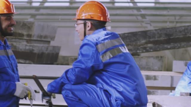 vídeos y material grabado en eventos de stock de equipo multirracial que trabaja en ferroconcrete factory - brigada