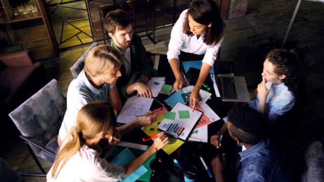 vídeos y material grabado en eventos de stock de multirracial es analizar el diagrama y escribir en etiquetas engomadas sentado en el escritorio en la habitación de la oficina. vista de ángulo alto de personas hablando, apuntando a gráficos y tomar notas. - eventos de etiqueta