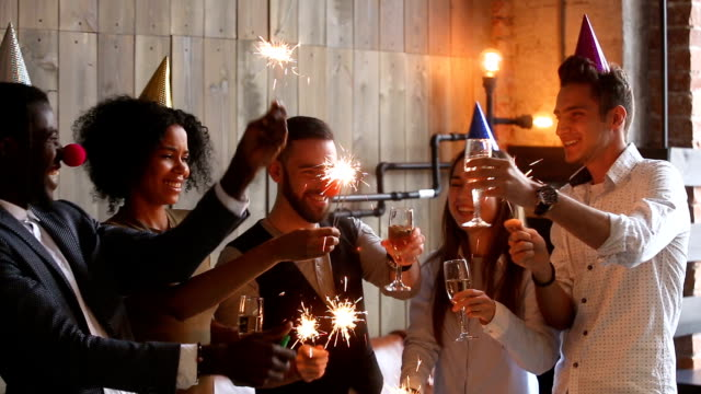 multiracial young people holding sparklers clinking glasses celebrating party, cheers - data scritta video stock e b–roll
