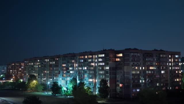 multistorey building with changing window lighting at night. timelapse - район стоковые видео и кадры b-roll