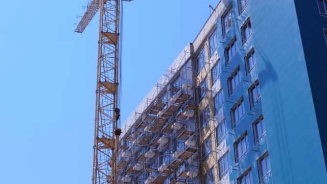 Multi-storey house under construction next to the construction crane. video