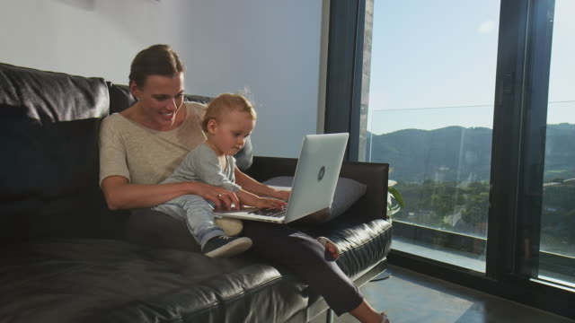 Multitasking businesswoman with her son at home Businesswoman using laptop while sitting with son. Multi-tasking female showing baby boy on sofa. They are at home. mid adult stock videos & royalty-free footage