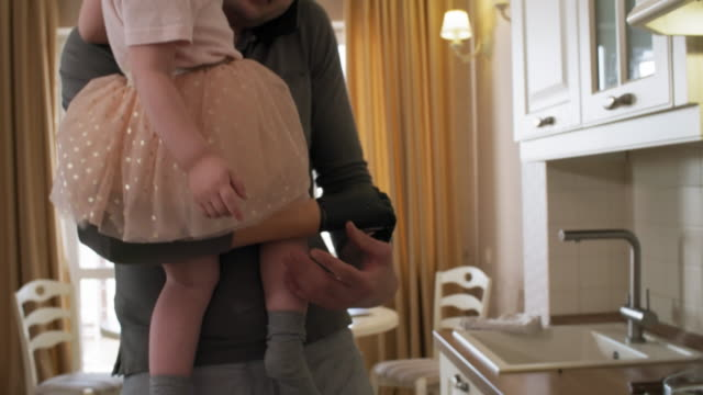 Multitasking Caucasian Handicapped Father Making Lunch with Daughter Tilting medium shot of multitasking amputee father holding up young daughter with myoelectric arm and preparing vegetable salad for lunch while talking on phone pressed between ear and shoulder amputee stock videos & royalty-free footage
