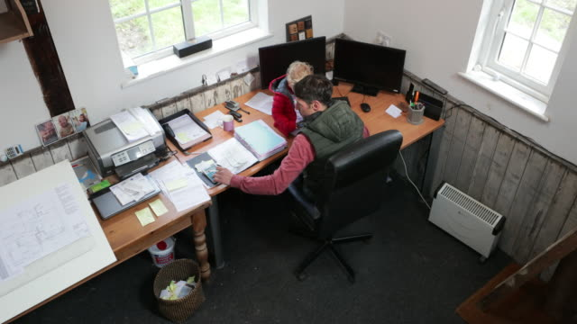 Multitasking Home life and Work Life Father working at an office using a caclclator while his daughter sits on the desk in front of him playing on a mobile phone. passion stock videos & royalty-free footage