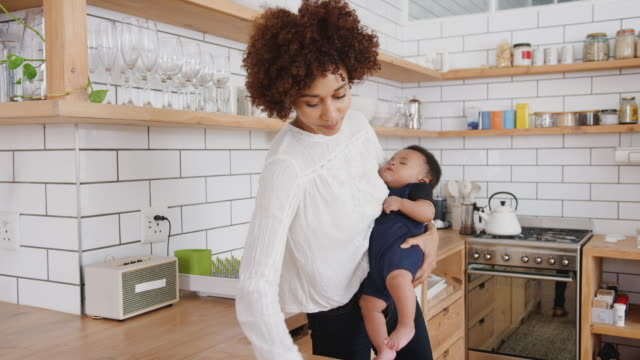 Multi-Tasking Mother Holds Sleeping Baby Son Whilst Cleaning And Working On Laptop In Kitchen Busy mother holding sleeping baby son wipes surfaces in kitchen before opening and working on laptop - shot in slow motion chores stock videos & royalty-free footage