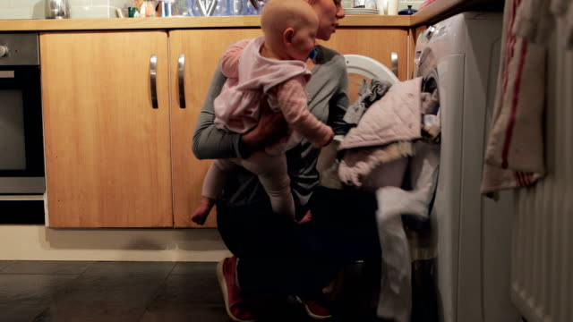 Multi-Tasking Mother Young mother is holding her crying baby daughter on her hip while trying to load the washing machine. chores stock videos & royalty-free footage