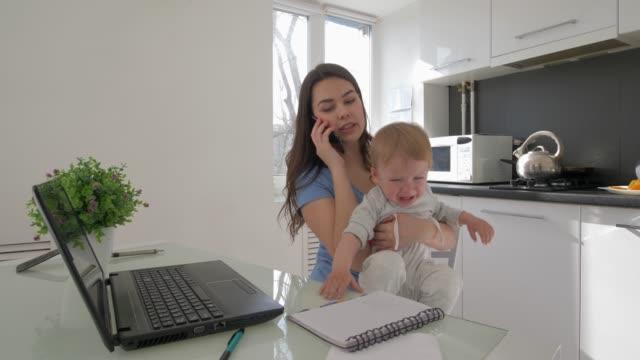 stockvideo's en b-roll-footage met multitasking moeder met huilende baby jongen tijdens het werken op laptop computer en praten over smartphone zittend aan tafel in de keuken - gewichten