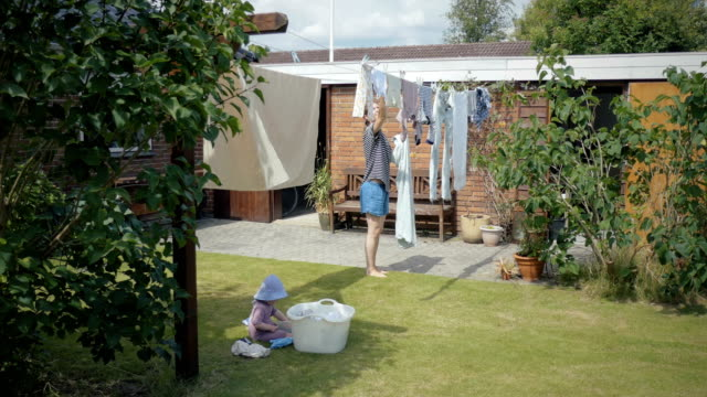 Mum and daghter doing laundry Cute toddler girl helping her mother hanging up laundry outside in the garden of a typical Danish home denmark stock videos & royalty-free footage