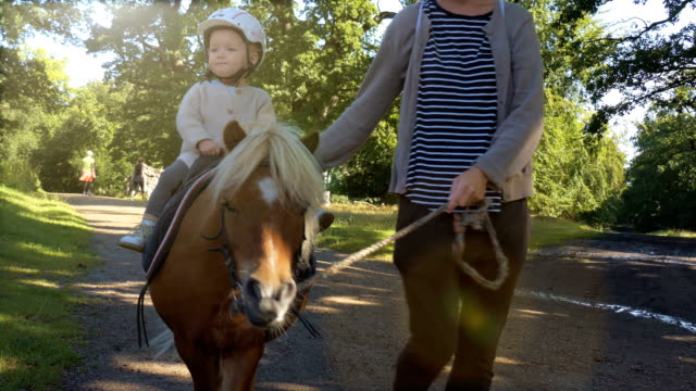 Mum and daughter riding on pony