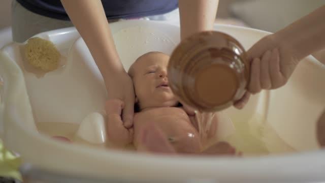 mama und oma baden baby - vollzeit elternteil stock-videos und b-roll-filmmaterial