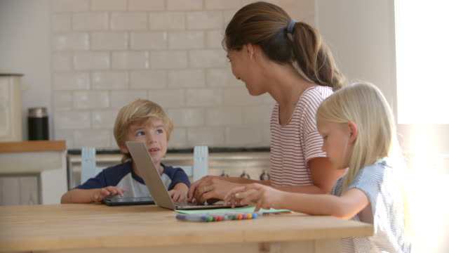 Mum and kids using computers and drawing at kitchen table - Vidéo