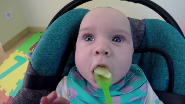 vídeos y material grabado en eventos de stock de mamá alimenta a un niño pequeño de una cuchara con puré de papas de frutas. 4k - nuevo bebé