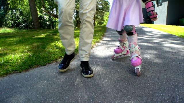 Mum Helps her Little Daughter to Skate on Roller Skates video