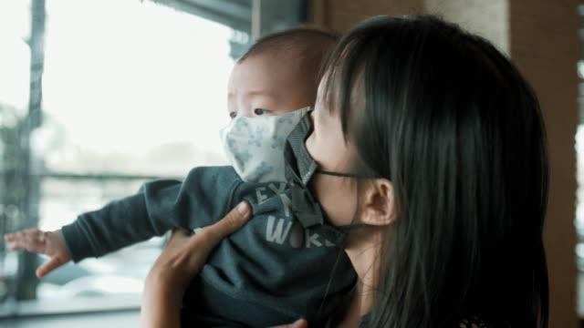 ママは彼女の息子を保持し、大気汚染マスクを着用 - マスク点の映像素材/bロール