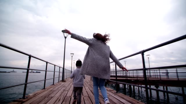 Mum playing and running with little son on a pier Little boy running and playing aeroplanes with his mother on a pier mothers day stock videos & royalty-free footage