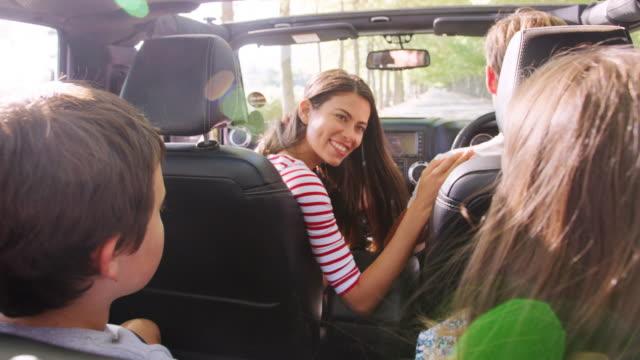 vídeos y material grabado en eventos de stock de mamá dando la vuelta para hablar con los niños en la parte trasera del coche - viajes familiares