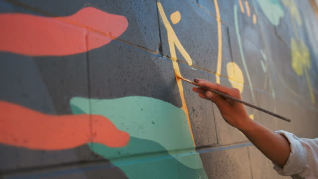 Mural artist at work Young Asian woman, mural artist creating wall art at the urban setting. art product stock videos & royalty-free footage
