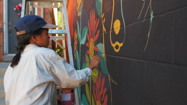 Mural artist at work Young Asian woman, mural artist creating wall art at the urban setting. mural stock videos & royalty-free footage
