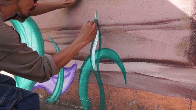 Mural artist painter paints leaves Mural artist painter paints leaves on school wall mural stock videos & royalty-free footage