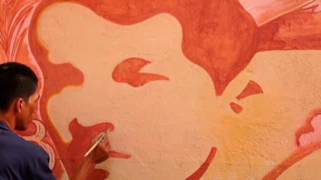 väggmålning målare ritar ett mänskligt ansikte bild på skolan vägg. - väggmålning bildbanksvideor och videomaterial från bakom kulisserna