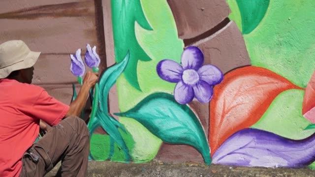 väggmålning målare ritar trädgården på skolan väggen - väggmålning bildbanksvideor och videomaterial från bakom kulisserna