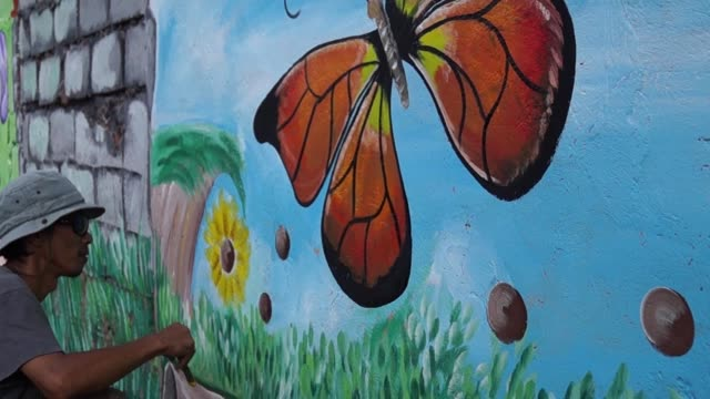 Mural painter paints butterfly in color on school wall. time lapse Mural painter paints butterfly in color on school wall. time lapse mural stock videos & royalty-free footage