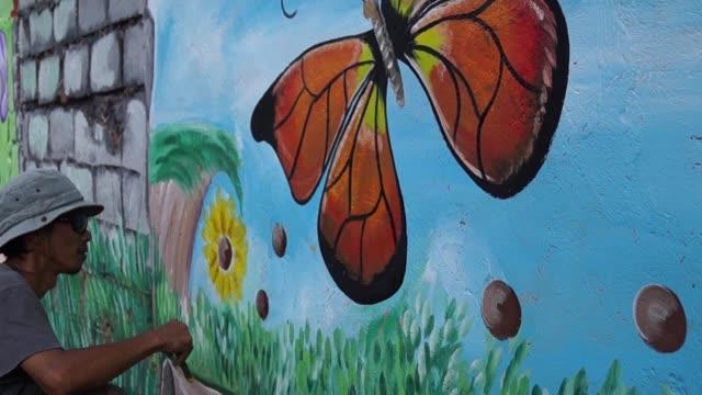 väggmålning målare målar fjäril i färg på skolan vägg. tidsfördröjning - väggmålning bildbanksvideor och videomaterial från bakom kulisserna