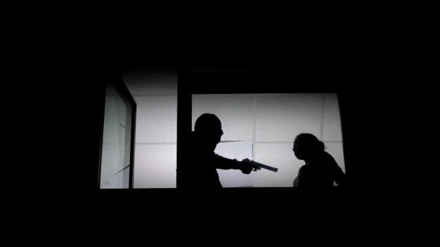 assassino in maschera passamontagna uccidendo donna con pistola, sagome in finestra, delitto - cadavere video stock e b–roll