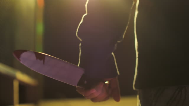 vidéos et rushes de main mâle de meurtrier avec un gros plan rapproché de couteau - lame