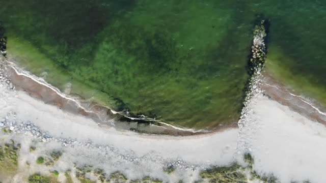 Murky waters lapping the shore of a white sands beach with rock groynes installed to prevent coastal errosion. Aerial view of the ocean