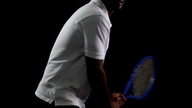 黒の背景、遅いボールを打つ白ポロで筋肉テニス選手 - テニス点の映像素材/bロール