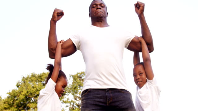 Muscled man holding his children video