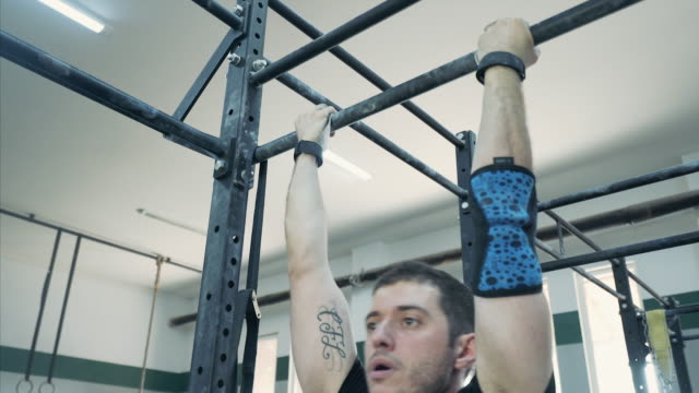 Musculair and confident man doing pullups at the gym. video