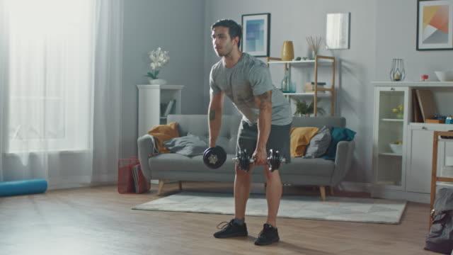 muskulöser athletic fit mann in t-shirt und shorts ist tun übungen mit hanteln zu hause in seinem geräumigen und helle wohnzimmer mit minimalistisches interieur. - hantel stock-videos und b-roll-filmmaterial